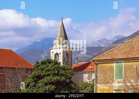 Mediterranean village: red tiled roofs  and bell tower against sky and mountains. Montenegro, Tivat, Donja Lastva village, Catholic Church of Saint Ro