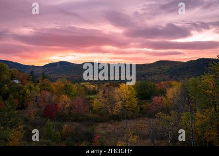 Dramatic autumn sunset over a wooden mountains at the peak of fall foliage