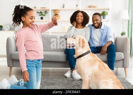 Black girl giving a treat to her obedient dog