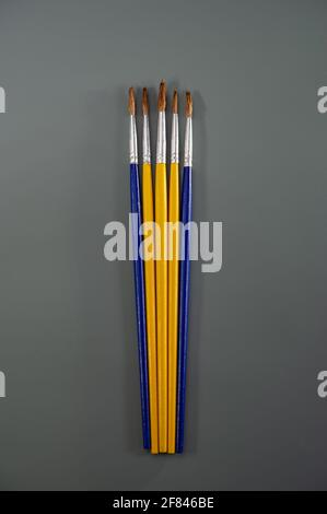 Artistic brushes lie on a dark gray background. Art concept. Cover.