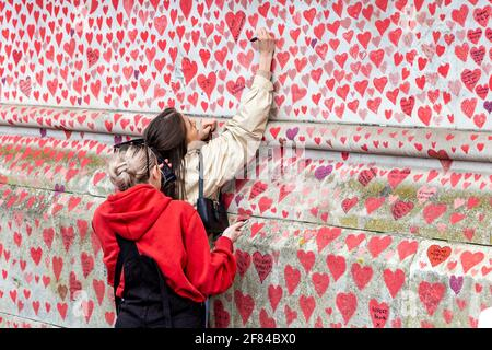 11 April 2021, London, UK - Woman signing The National COVID Memorial Wall on the South Bank which has hearts drawn and names of those who died in the coronavirus pandemic