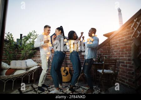 Multiracial men and women dancing on roof with glowing garlands on neck. Four happy friends in casual clothes hanging out together during weekends.
