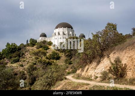 Looking up at Griffith Observatory from east hiking trail in Griffith Park, a popular loop for exercise with social distancing in Los Angeles - Stock Photo