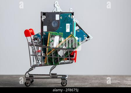 A concept image with a small shopping cart filled with computer parts including RAM memory cards and a hard drive. Shopping for technology, consumer e