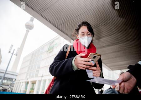 Berlin, Germany. 12th Apr, 2021. A customer scans a QR code at the entrance of a clothing store at Alexanderplatz in front of a security guard using the Luca app. The app is used to provide data for possible contact tracing. Credit: Christoph Soeder/dpa/Alamy Live News
