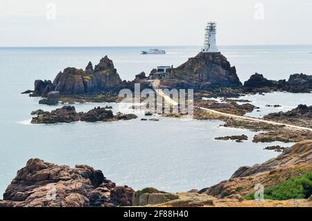 Jersey, UK - June 09, 2011: Unidentified people on causeway to this small, rocky island with a lighthouse at La Corbiere, accessible only with low tid