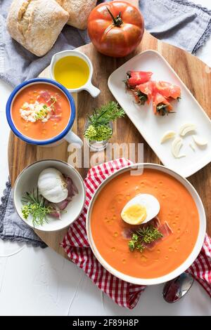 Closeup view of a cold spanish tomato soup ingredients on a wooden cutting board.