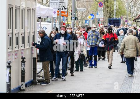 Berlin, Germany. 12th Apr, 2021. People wait for COVID-19 tests outside a test site in Berlin, capital of Germany, on April 12, 2021. More than three million COVID-19 infections have been registered in Germany on Monday since the outbreak of the pandemic, according to the Robert Koch Institute (RKI). Credit: Stefan Zeitz/Xinhua/Alamy Live News