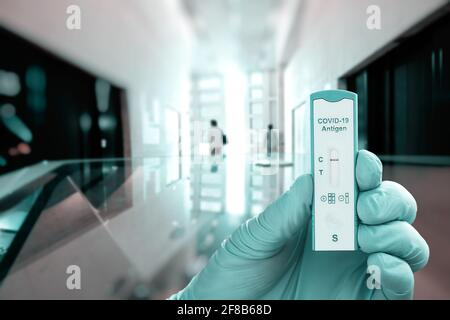 Hand in protective glove hold express COVID-19 antigen test for quick testing of coronavirus infection on abstract geometric architectural background - Stock Photo