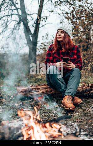 Traveler girl in hipster clothes sits on a log enjoying, relaxing in the forest near the fire by camping. Woman using smartphone in nature