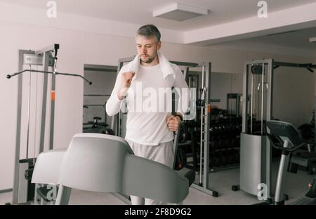 tall young man in sports clothes running on a treadmill in the gym