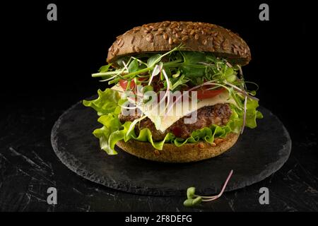 closed sandwich in a bun with cucumber, tomato and microgreens. Homemade burger. Stock Photo
