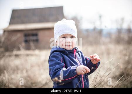 A child in the background of a rural abandoned house. Destroyed not an apartment building in the village. Walking in nature.