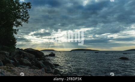 Evening landscape on the White Sea. Shoreline with stone boulders. The sun's rays breaking through the clouds. Cloudy sky over the sea surface. The im