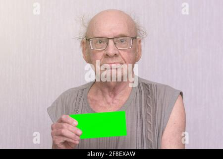 Old retired bald man with eyeglasses in gray shirt is blank in his hand.
