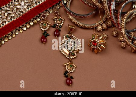 Antique jewellery on a brown background, Golden scarf, Gold bracelet, Gold necklace, Gold earrings, finger ring indian traditional jewellery