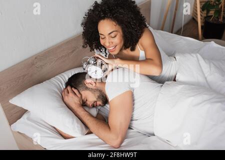 happy african american woman holding alarm clock near displeased man sleeping on bed