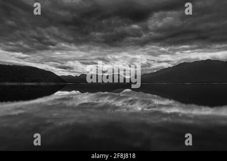 Black and white photo of mountains and storm clouds reflected in Lake Burbury in Tasmania, Australia, on the edge of Tasmania's World Heritage Wildern