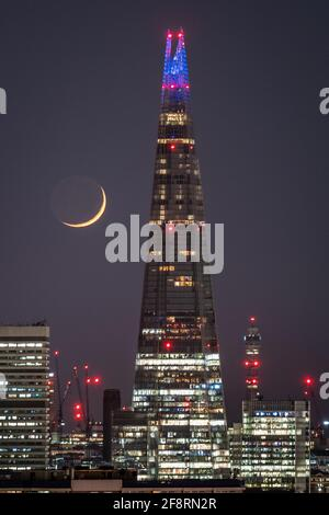 London, UK. 14th April, 2021. UK Weather: A Waxing Crescent moon sets in the late hours of Wednesday moving past The Shard skyscraper building following a north westerly direction. Credit: Guy Corbishley/Alamy Live News