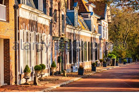 Wassenaar, Netherlands - November 06 2020 : a row of typical dutch houses and the facades along a small countryside road - Stock Photo