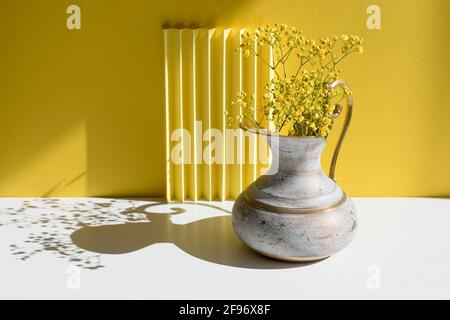 A bouquet of Gypsophila in a brass jug with harsh shadow. Minimal interior decoration concept. Minimal summer concept. Copy space.