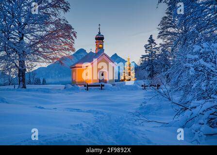 Winter landscape with Maria Rast chapel on the Buckelwiesen against Arnspitzgruppe (2198m) in the Wetterstein Mountains, Krün, Werdenfelser Land, Upper Bavaria, Bavaria, Germany - Stock Photo