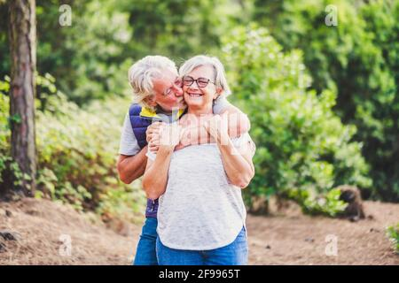 Happiness and love relationship. couple of old people man and woman senior hog and kiss in outdoor park - elderly retired lifestyle and joyful - concept of together forever and outdoor leisure