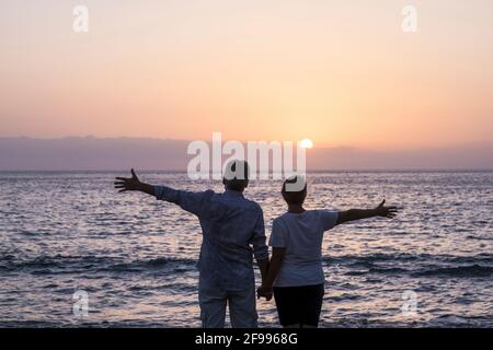 Happy senior couple people in love enjoy a sunset on the ocean holding hands - ñpve and relationship elderly summer holiday lifestyle man and woman together in happiness looking the sea