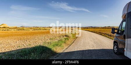 Motorhome on a dust road in a desert landscape