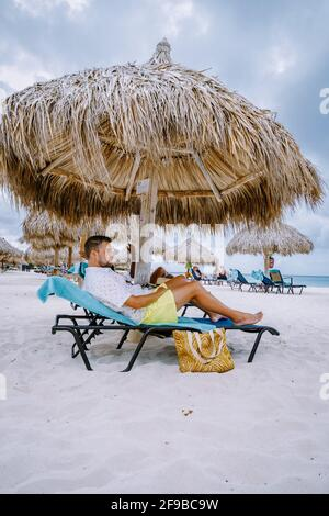 Aruba Caribbean couple man and woman mid age on vacation on the beach with palm trees on the beach Stock Photo