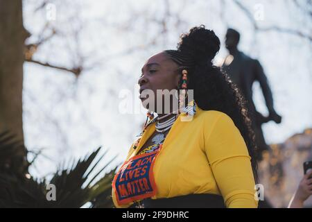 Westminster, London | UK -  2021.04.17: Lady in yellow costume with Black Lives Matter sign giving a speach at the Kill the Bill protest