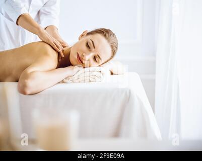 Beautiful woman enjoying back massage with closed eyes. Spa treatment concept.