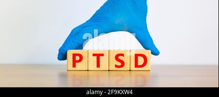 PTSD, post-traumatic stress disorder symbol. Concept words 'PTSD, post-traumatic stress disorder' on cubes on a beautiful white background. Doctor han