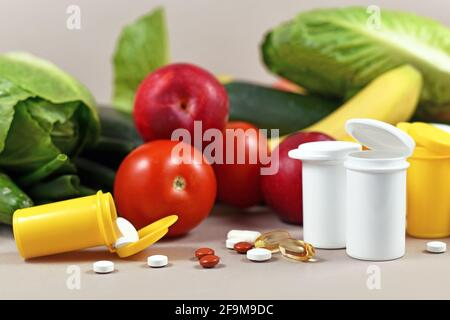 Bottles with pills of food nutrition supplements in front of fruits and vegetables in background - Stock Photo