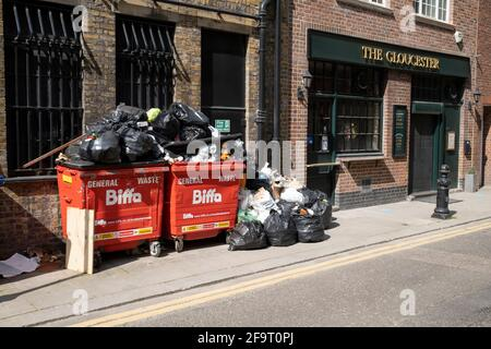 Piles of rubbish and recycling in and around bins outside a pub in Knightsbridge on 14th April 2021 in London, United Kingdom.