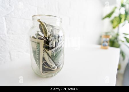 Folding money in a jar on a white wooden background. The background image place for text.