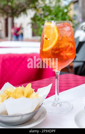 glass of aperol spritz cocktail on outside table on sunny day with bowl of potato chips in foreground