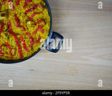 Traditional spanish seafood paella with pork sausages, pork ribs and red peppers in frying pan on a wooden table and a napkin - Stock Photo