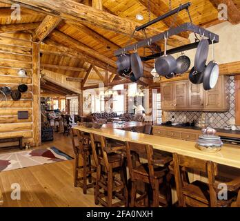 The kitchen with bar counter, pot rack, and rustic cabinetry, in a modern log cabin in the mountains