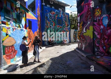 Sao Paulo, Brazil. 21st Apr, 2021. People visit the place called Beco do Batman in Sao Paulo, a place well known for the paintings on the walls by artists from the region. Recently the place was all painted black in protest of the death of Nego Vila. (Photo by Ronaldo Silva/Pacific Press) Credit: Pacific Press Media Production Corp./Alamy Live News