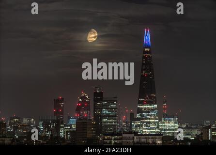 London, UK. 22nd April, 2021. UK Weather: A 75% Waxing Gibbous moon continues to set in the early hours of Thursday moving behind The Shard skyscraper building following a westerly north direction. Credit: Guy Corbishley/Alamy Live News