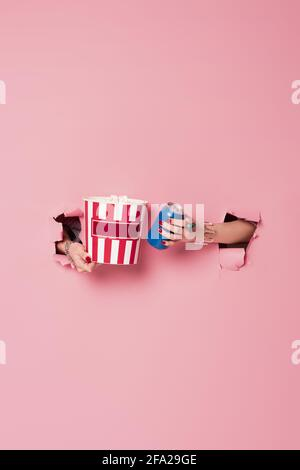 Cropped view of woman holding canned drink and popcorn in holes of pink background