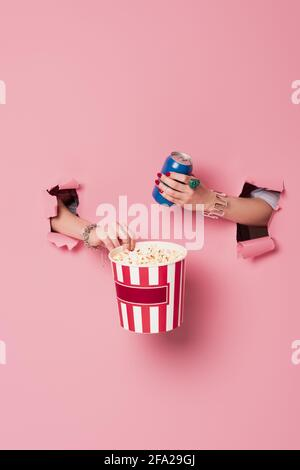 Cropped view of woman holding popcorn and drink in can near pink background with holes