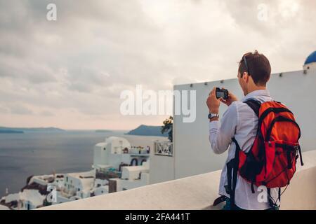 Santorini traveler man taking photo of Caldera from Oia, Greece on camera. Backpacker travels during summer vacation. Tourist admiring Aegean sea land