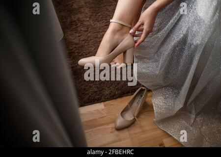 young beautiful woman bride puts on beautiful shoes on a wedding day.