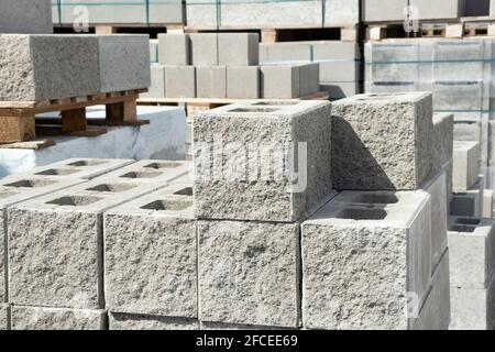 Stack of cement concrete Building cinder blocks brick  on pallete in hardware store with decorative stone texture side