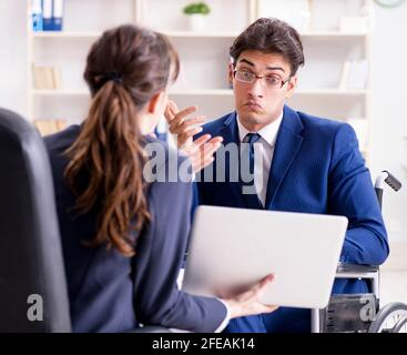 The disabled businessman having discussion with female colleague