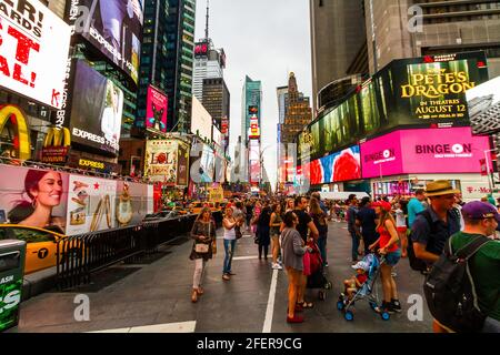 Tourist in summer outfits taking photos at Times Square on a busy evening