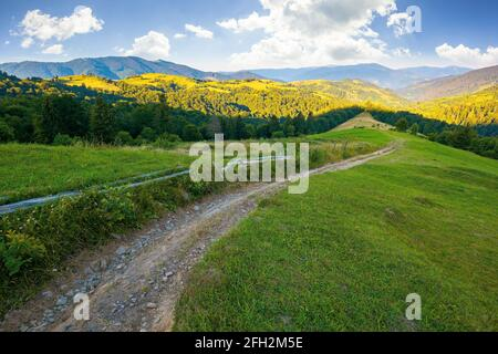 rural landscape in mountains at summer sunrise. country road through grassy pasture winding down in to the distant valley. clouds on the blue sky abov