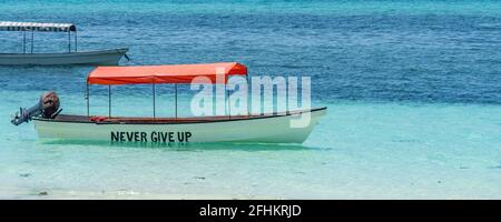 Boat at the beach on Zanzibar Island with the writing never give up with stunning turquoise water, panorama